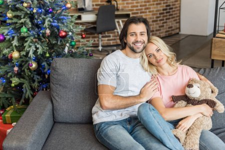 Photo for High angle view of beautiful happy young couple sitting on couch and smiling at camera at christmas time - Royalty Free Image