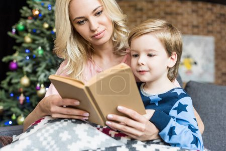 mother and cute little son reading book together at christmas time