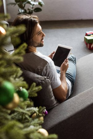 Photo for High angle view of smiling young man using digital tablet with blank screen at christmas time - Royalty Free Image