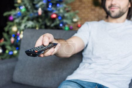 close-up view of man using remote controller while sitting on couch at christmas time