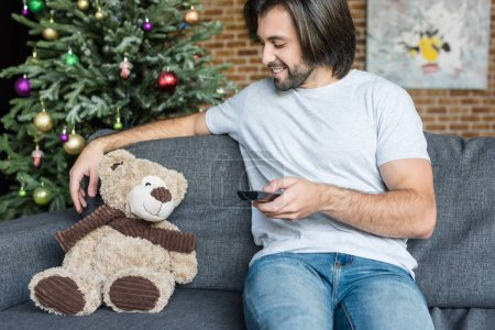 Foto de Sonriente hombre sosteniendo el mando a distancia y mirar osito en el sofá en Navidad - Imagen libre de derechos