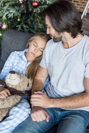high angle view of father and cute daughter in pajamas holding teddy bear and sleeping on couch at christmas time