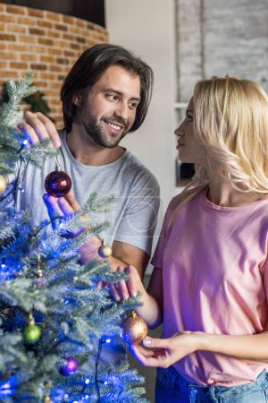 happy young couple decorating christmas tree and looking at each other