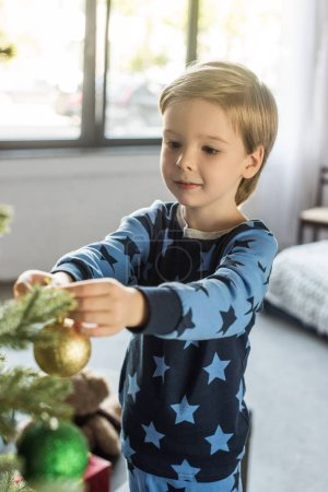 cute smiling little boy in pajamas decorating christmas tree