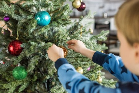 cropped shot of child in pajamas decorating christmas tree