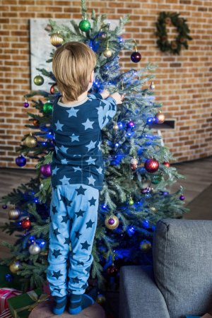 back view of cute little boy in pajamas decorating christmas tree