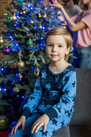 Photo for Adorable little boy in pajamas sitting on sofa and smiling at camera at christmas time - Royalty Free Image