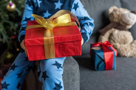 Photo for Cropped shot of child in pajamas sitting on couch and holding christmas present - Royalty Free Image