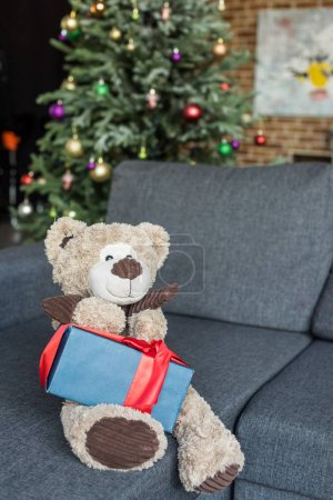 teddy bear with present on couch and decorated christmas tree behind