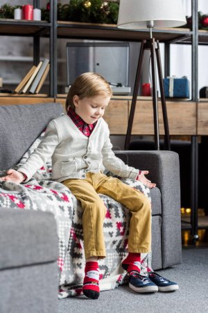 cute smiling child sitting on sofa and looking at shoes
