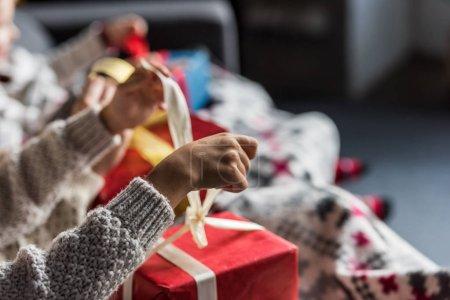 Photo pour Vue partielle du couple en chandails d'hiver ouvrant cadeaux de Noël - image libre de droit