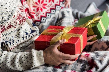 Photo pour Plan recadré de jeune couple en chandails d'hiver tenant des cadeaux de Noël - image libre de droit