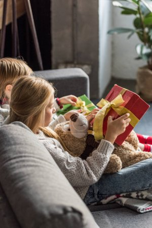 side view of children sitting on couch and opening christmas gifts