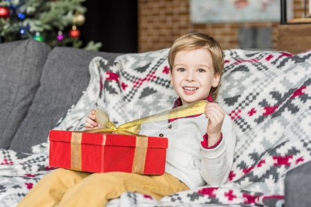 cute happy little boy opening christmas gift and smiling at camera