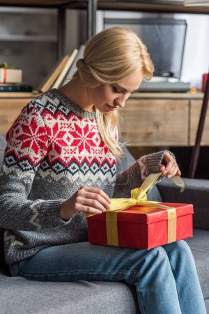 beautiful young blonde woman opening christmas present at home