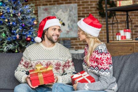Photo pour Jeune couple heureux chapeaux santa holding des cadeaux de Noël et souriant mutuellement - image libre de droit