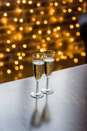 vue rapprochée de deux verres de champagne et fond de bokeh doré