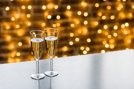 close-up view of two glasses of champagne and beautiful christmas background