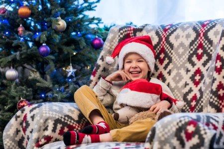 Foto de Adorable niño alegre celebración de oso de peluche en el sombrero de santa y sonriendo a cámara - Imagen libre de derechos