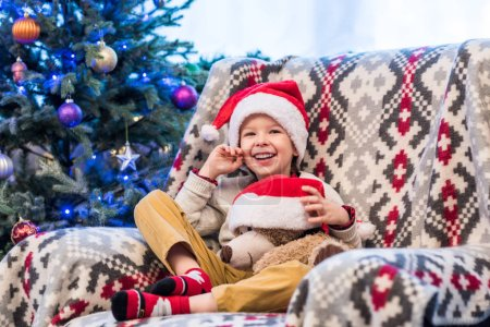 happy little boy holding teddy bear in santa hat and smiling at camera