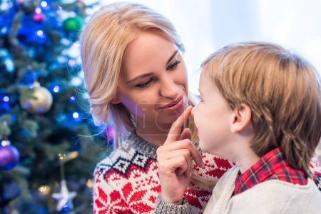 Photo for Beautiful happy young mother looking at adorable little son at christmas time - Royalty Free Image