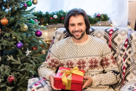 happy young man holding christmas gift and smiling at camera