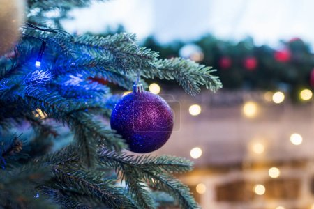 close-up view of beautiful shiny purple ball hanging on christmas tree
