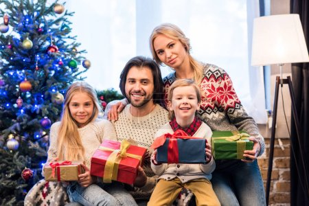 happy family in sweaters holding christmas presents and smiling at camera