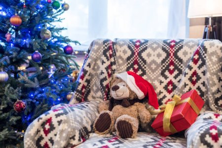 teddy bear in santa hat and gift box on sofa and decorated christmas tree behind