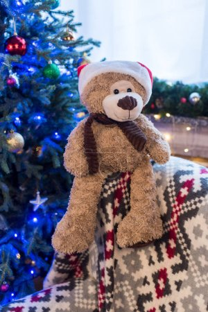 close-up view of teddy bear in santa hat and beautiful decorated christmas tree behind