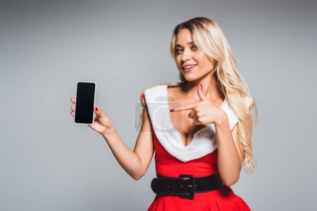 Photo for Attractive woman in christmas dress pointing by finger at smartphone with blank screen isolated on grey background - Royalty Free Image