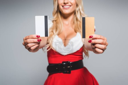 partial view of young woman in christmas dress showing credit cards isolated on grey background