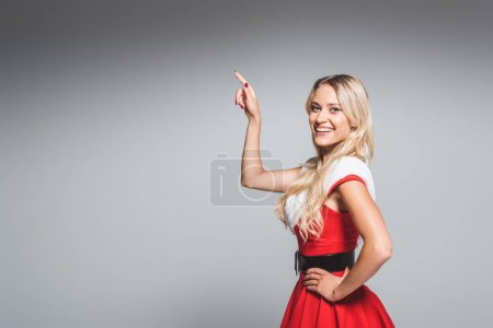laughing young woman in christmas dress pointing by finger isolated on grey background