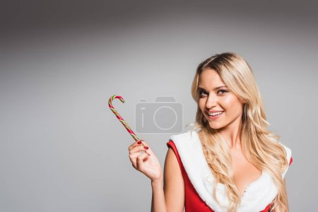 smiling young woman in santa dress showing striped christmas stick isolated on grey background