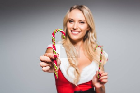 Photo for Selective focus of young woman in santa dress showing striped christmas sticks isolated on grey background - Royalty Free Image