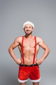 happy muscular shirtless man in christmas hat and shorts standing with hands on waist isolated on grey background
