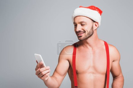 muscular man in christmas hat looking at smartphone isolated on grey background