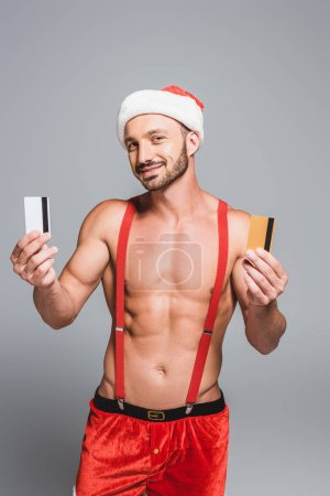 handsome muscular man in christmas hat showing credit cards isolated on grey background