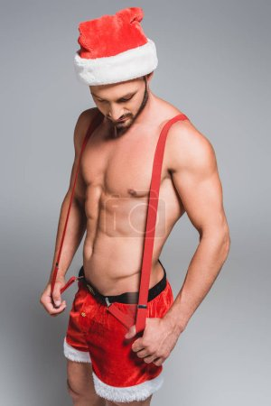 handsome muscular man in christmas hat holding suspenders and looking down isolated on grey background