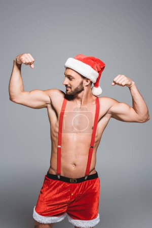 sexy muscular man in christmas hat showing muscles isolated on grey background