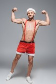 young muscular man in christmas hat showing muscles isolated on grey background