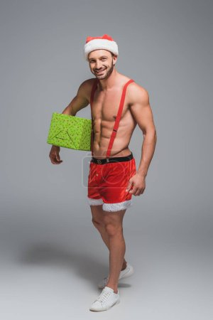 smiling muscular man in christmas hat and shorts holding gift box isolated on grey background