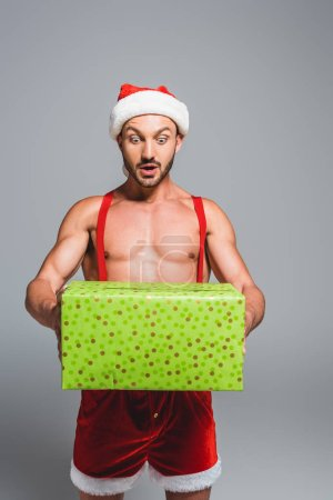 shocked muscular man in christmas hat holding gift box isolated on grey background