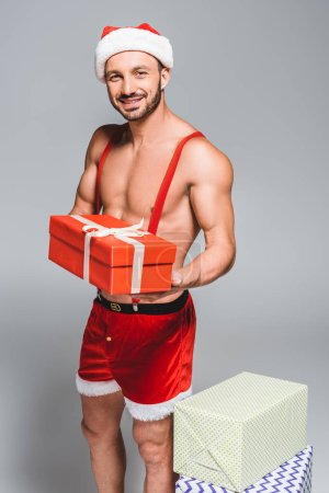 Photo for Happy muscular santa in christmas hat and shorts holding gift box isolated on grey background - Royalty Free Image