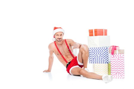 muscular shirtless man in christmas hat sitting near pile of gift boxes isolated on white background