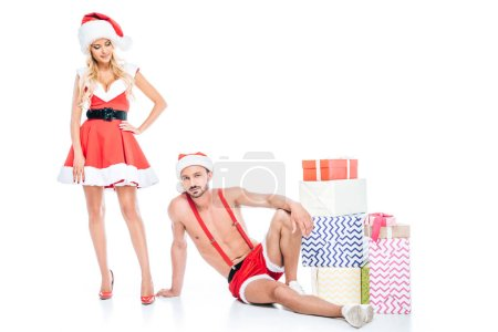 young muscular shirtless man in christmas hat laying on floor while his girlfriend standing near pile of gift boxes isolated on white background
