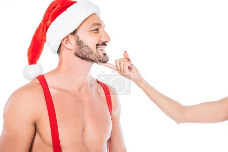 cropped image of woman touching chin of her shirtless muscular boyfriend in christmas hat isolated on white background