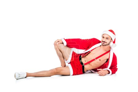handsome muscular man in santa claus costume and shorts laying on floor isolated on white background