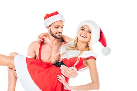 young muscular shirtless man in christmas hat holding happy girlfriend on hands isolated on white background