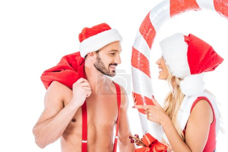 happy muscular shirtless man in santa hat and attractive young woman with striped christmas stick isolated on white background